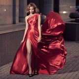 Young Beautiful Woman In Fluttering Red Dress. City Background. Stock Image