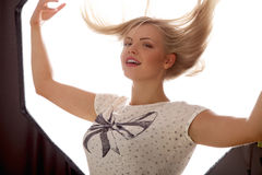 Young beautiful woman flying hair smiling in front of studio flash light Royalty Free Stock Photo