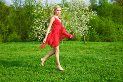 Young beautiful woman flying over the green grass. In a red dress Stock Photos