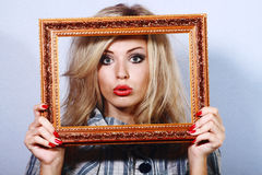 Young beautiful woman in a frame. Young beautiful woman with red lips holding a frame in front of her face stock photos