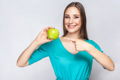 Young beautiful woman with freckles and green dress holding apple and pointing with finger. Royalty Free Stock Photo