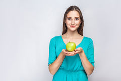 Young beautiful woman with freckles and green dress holding apple and sharing with smile. Stock Images