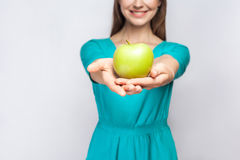 Young beautiful woman with freckles and green dress holding apple and sharing with smile. Royalty Free Stock Images