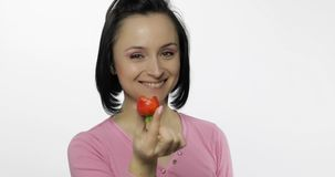 Young beautiful woman with fresh and juicy strawberry offer bite to viewer royalty free stock image