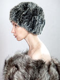 The young beautiful woman in a fur hat in a profil. The young beautiful woman in a fur hat Stock Image