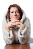 Young beautiful woman in the fur sitting at the ta Royalty Free Stock Image