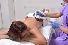 Young beautiful woman gets professional skin treatment in a beau. Ty clinic. Body shaper Royalty Free Stock Photo
