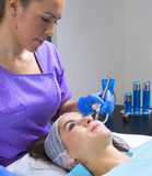 Young beautiful woman gets professional skin treatment in a beauty clinic. Beautiful women gets professional skin treatment Royalty Free Stock Images