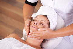 Young beautiful woman getting facial massage Stock Photo