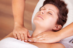 Young beautiful woman getting shoulders massage Stock Images