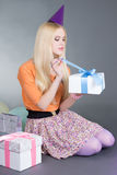 Young beautiful woman with gift. Over grey Stock Photos