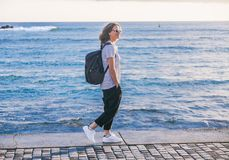 Young beautiful woman girl with a backpack walks along the seash Royalty Free Stock Photography
