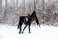 Young beautiful woman girl in black ballet suit presents herself in snowy winter forest royalty free stock photography