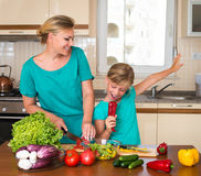 Young beautiful woman and girl making fresh vegetable salad. Healthy domestic food concept. Smiling mother and funny playful daugh Stock Photos