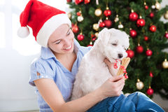 Young beautiful woman gives present bone to her dog for christma Royalty Free Stock Image