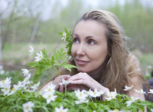Young beautiful woman on a glade of blossoming snowdrops Stock Photo