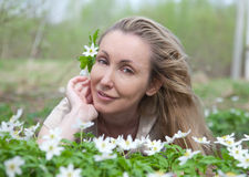 Young beautiful woman on a glade of blossoming snowdrops in the early spring Stock Images