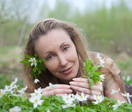 The young beautiful woman on a glade of blossoming snowdrops Royalty Free Stock Photos
