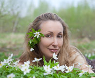 The young beautiful woman on a glade of blossoming snowdrops Stock Images