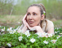 Young beautiful woman on a glade of blossoming snowdrops in the early spring Stock Photo