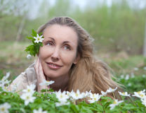 The young beautiful woman on a glade of blossoming snowdrops Royalty Free Stock Photography
