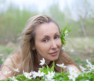 Young beautiful woman on a glade of blossoming snowdrops in the early spring Stock Photography