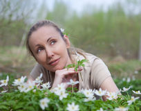 The young beautiful woman on a glade of blossoming snowdrops in the early spring Royalty Free Stock Photo