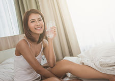 Young beautiful woman with glass of water in a bed. Smiling woman laying in the hotel room,bedroom. stock photography
