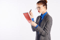 Young beautiful woman in glasses checks homework, emotions, teacher, white isolated background Stock Image