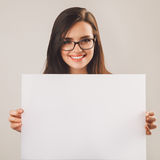 Young beautiful woman in glasses holding white blank board Stock Photos
