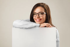 Young beautiful woman in glasses holding white blank board Royalty Free Stock Photo