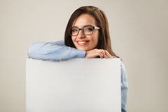 Young beautiful woman in glasses holding white blank board Royalty Free Stock Photos