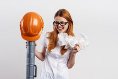 Young beautiful woman in glasses on a light background holds blueprints, engineer Stock Images
