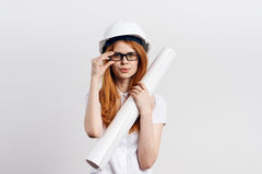 Young beautiful woman in glasses on a light background holds blueprints, engineer, construction Royalty Free Stock Photography