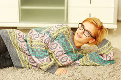 Young beautiful woman in glasses lying on the carpet Royalty Free Stock Photo
