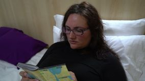 Young beautiful woman in glasses reading in bed. Young beautiful woman using on bed and holding smartphone stock video footage
