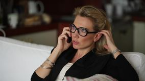 Young beautiful woman in glasses sitting and talking on the cell phone. Work. stock footage