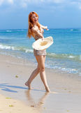 Young beautiful woman goes on ocean coast with straw hat in hands Royalty Free Stock Images