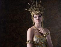 Beautiful woman in a gold dress and crown Royalty Free Stock Images