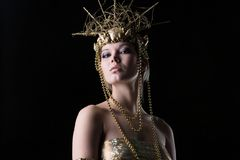 Beautiful woman in a gold dress and crown Royalty Free Stock Photo