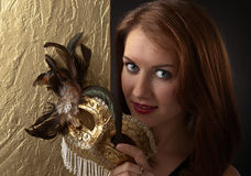 Young beautiful woman with golden carnival mask Royalty Free Stock Image