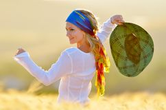 Young beautiful woman on golden cereal field Stock Photo