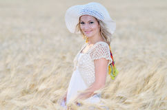 Young beautiful woman on golden cereal field in summer Stock Photo