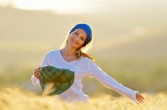Young beautiful woman on golden cereal field in summer Stock Photos