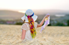 Young beautiful woman on golden cereal field in summer Royalty Free Stock Images