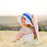 Young beautiful woman on golden cereal field in summer Stock Image