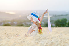 Young beautiful woman on golden cereal field in summer Stock Photography