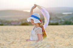 Young beautiful woman on golden cereal field in summer Royalty Free Stock Photos