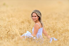 Young beautiful woman in golden wheat field Stock Photography