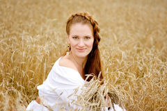 Young beautiful woman in golden wheat field Royalty Free Stock Photos